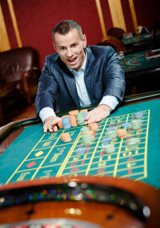 entertainment risk: Joyful gambler stakes playing roulette at the casino. Risky entertainment of gambling