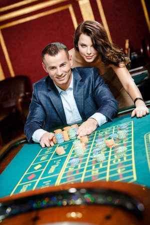 ruleta de casino: El hombre acompañado de apuestas mujer colocando en la mesa de la ruleta Foto de archivo