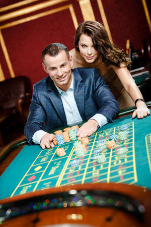 casino roulette: Man accompanied by woman placing bets at the roulette table Stock Photo