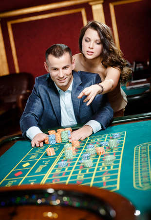 bets: Man accompanied by woman placing bets at the casino table