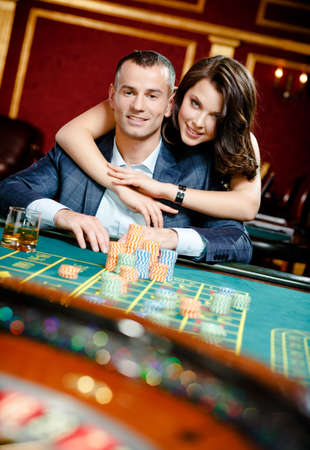 risky: Woman embracing gambler at the playing table. Player follows the risky game