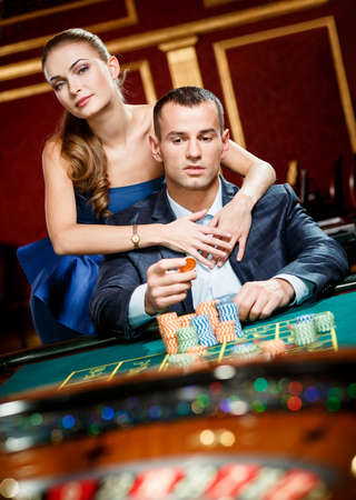 risky: Girl embracing gambler at the roulette table. Player follows the risky game Stock Photo