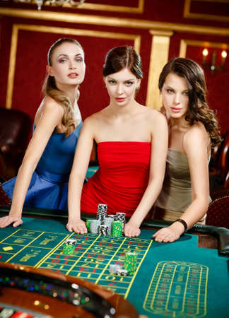 Three women place a bet playing roulette at the gambling house photo