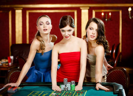 roulette table: Three women bet playing roulette at the gambling house Stock Photo