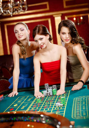Three women place a bet playing roulette at the casino club photo