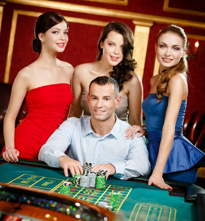 Man surrounded by women gambles roulette at the casino photo