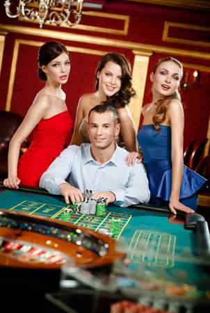 Man surrounded by girls gambles roulette at the casino photo