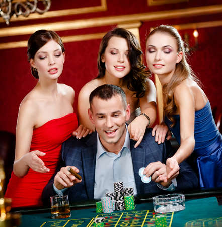 lucky man: Man surrounded by women plays roulette at the gambling house Stock Photo