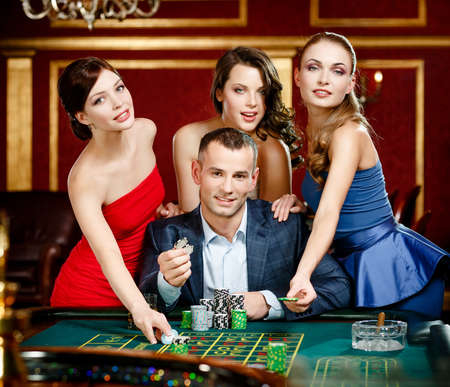 casino game: Man surrounded by women plays roulette at the casino club Stock Photo