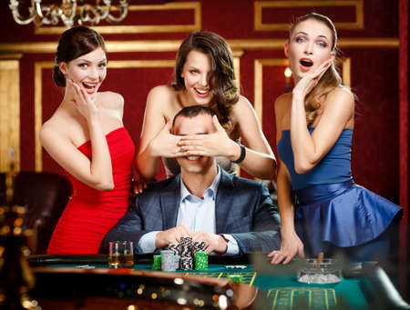 hands covering eyes: Girls cover the eyes of the gambler playing roulette at the casino Stock Photo