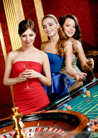 Women keeping glasses of spirits play roulette at the gambling house photo