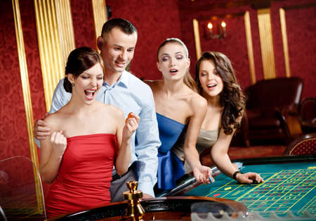 Group of young people playing roulette at the gambling house photo