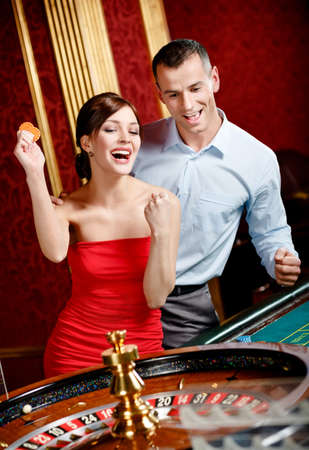 roulette player: Happy couple playing roulette wins at the casino club Stock Photo