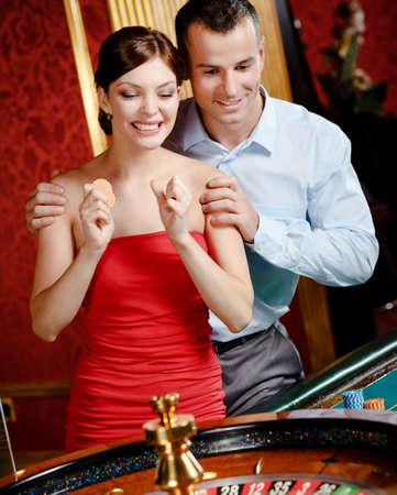 Couple playing roulette follows the game at the casino photo