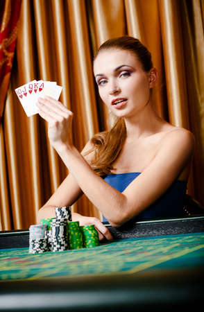 gambler: Portrait of the female gambler with cards and chips at the poker table