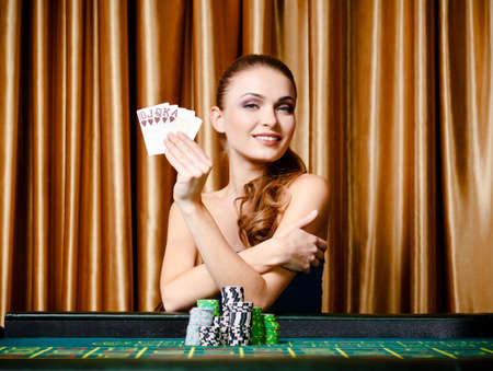Portrait of the female gambler at the poker table with cards photo