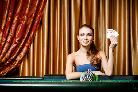 casino game: Portrait of the female gambler at the poker table handing cards