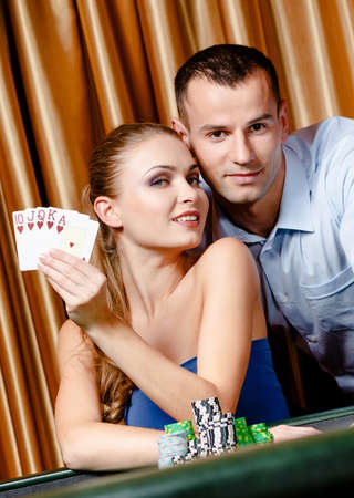 Couple playing poker at the gambling house. Woman keeps cards in hand photo