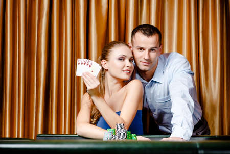 Young couple playing poker at the casino. Woman keeps cards in hand photo