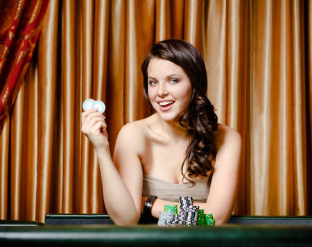 Portrait of smiley female gambler sitting at the roulette table with chips in hand photo