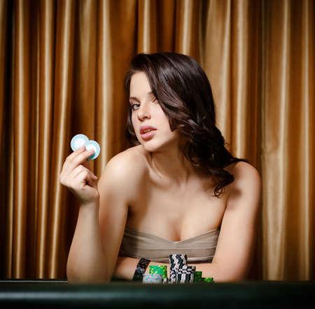roulette: Ritratto di giocatore femminile seduta al tavolo della roulette con chip in mano