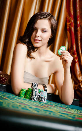 Portrait of female gambler sitting at the playing table with chips in hand photo