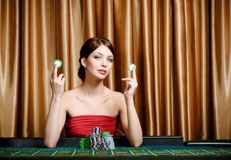 ruleta de casino: Mujer con chips de sentarse a la mesa del casino en el casino