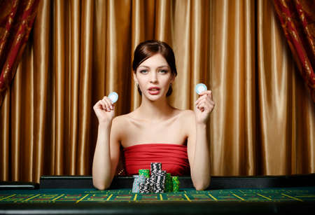 Woman with chips sitting at the roulette table at the gambling house photo