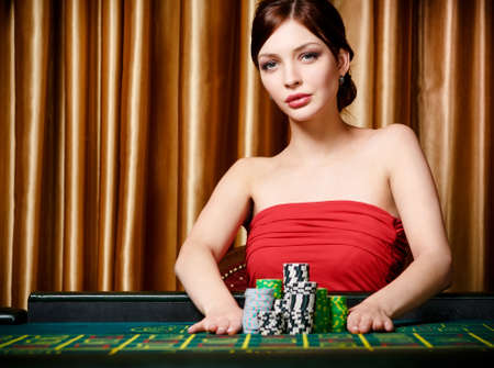 roulette player: Woman stakes piles of chips playing roulette at the casino club Stock Photo