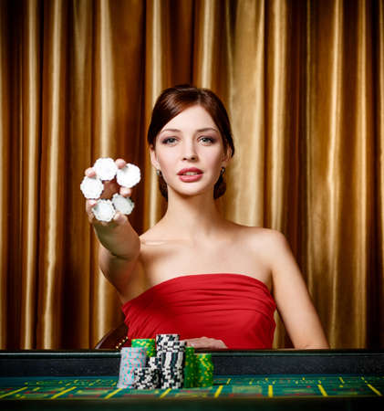 Female gambler keeps chips in hand sitting at the casino table photo