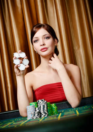 Female gambler keeps chips in hand sitting at the roulette table photo