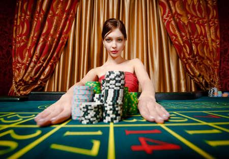 fichas casino: Mujer gana ruleta y quita las pilas de fichas en la casa de juego Foto de archivo