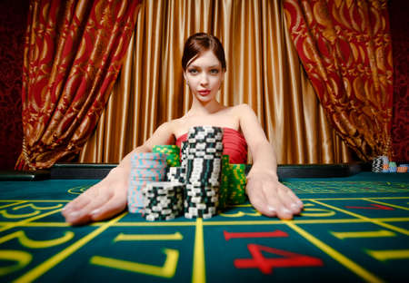 Woman wins roulette and takes away piles of chips at the gambling house photo