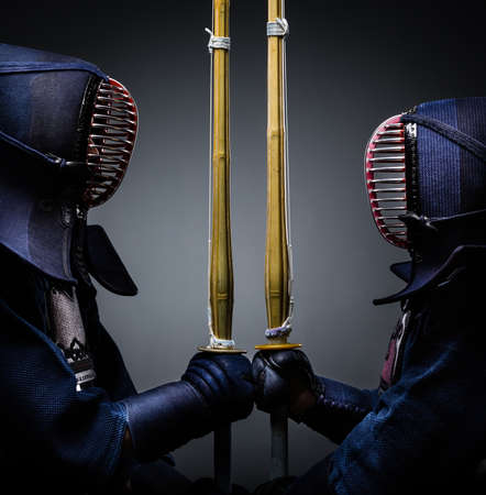 kendo: Two kendo fighters opposite each other with bokuto. Japanese martial art of sword fighting