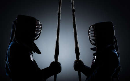 kendo: Two kendo fighters opposite each other with shinai. Japanese martial art of sword fighting