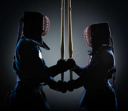Two kendoka opposite each other with wooden sword. Japanese martial art of sword fighting photo