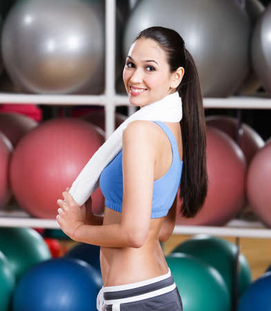 Sportswoman with ideal figure in fitness gym with shelves of gym balls Stock Photo - 17824307