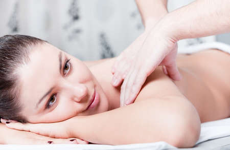 Woman receives body massage at spa photo