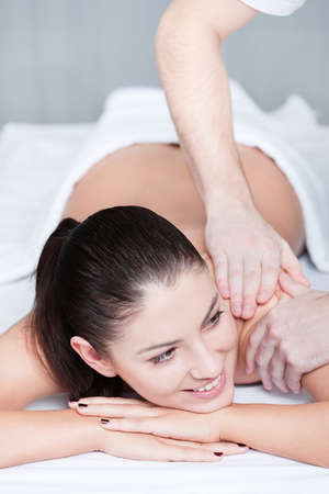 Relaxing massage for young beautiful woman at spa salon photo