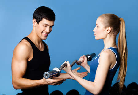 sports wear: Trainer shows woman the correct exercise performing with weight Stock Photo