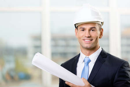 Engineer in white hard hat hands blueprint. Concept of successful construction
