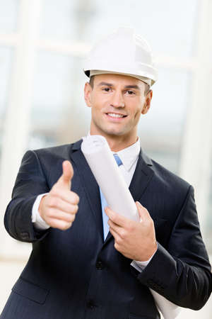 architecting: Engineer in white hard hat hands blueprint and thumbs up. Concept of successful construction