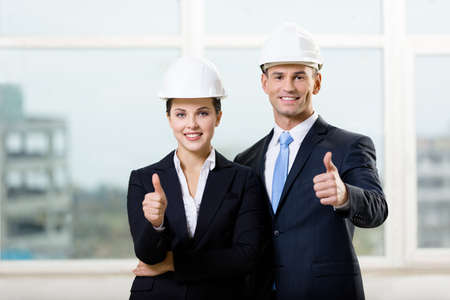 architecting: Portrait of two engineers standing near each other and thumbing up Stock Photo