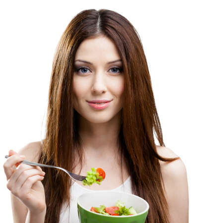 Dieting woman eats fresh salad in salad bowl, isolated on white