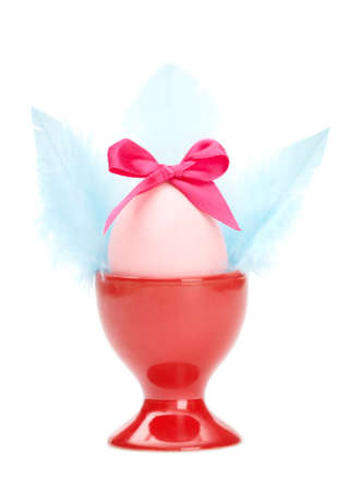 chucky: Colored easter egg with pink bow and blue wings in red egg cup, isolated on white. Traditional symbol of the feast