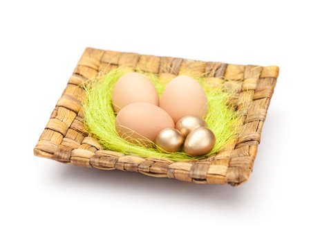 chucky: Brown and golden easter eggs are on wattled plate with sisal green fibre, isolated on white background