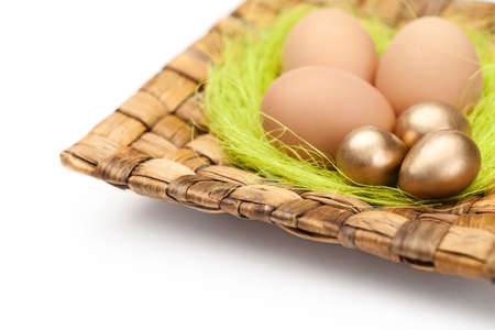 chucky: Brown and golden easter eggs are on wattled plate with sisal green fibre, isolated on a white background