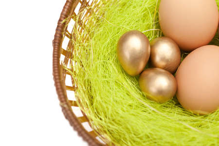Brown and golden easter eggs are in wattled basket with sisal fibre, isolated on white photo