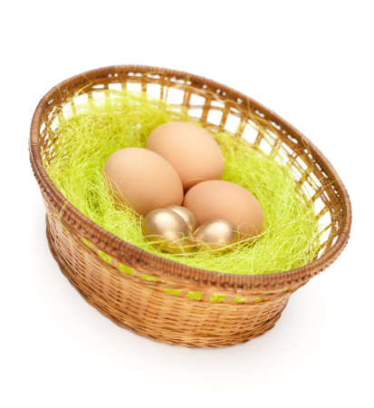 Brown and golden easter eggs are in wattled basket with sisal green fibre, isolated Stock Photo - 18042214