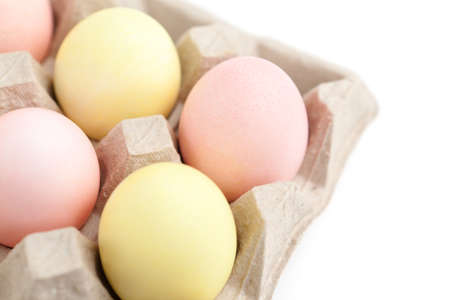 Colorful eggs are in the cardboard box for egg delivering, isolated on white photo
